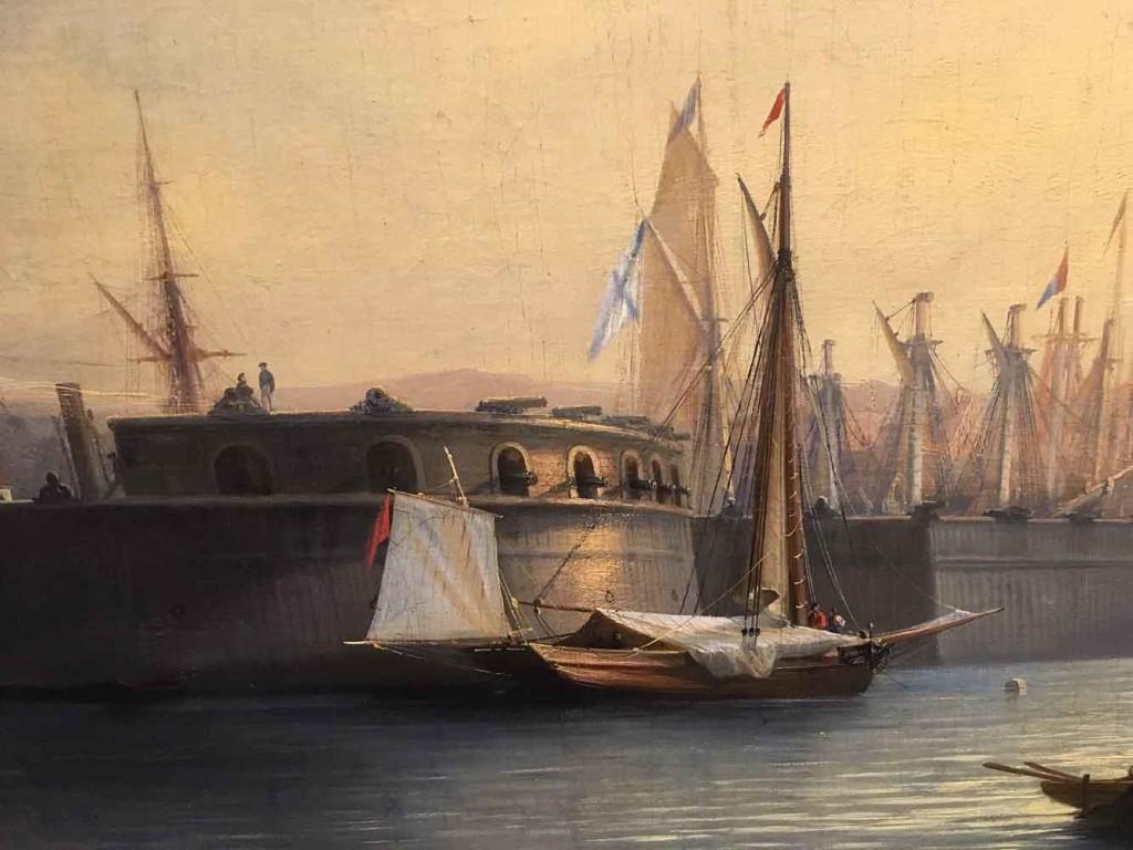 Sataman suojaksi oli rakennettu (nähtävästi hirsistä) suojamuuri ja jopa pieni kaareva linnoitus tykkeineen. Etualalla näkyvän pienemmän aluksen perässä liehuu punainen lippu, josta en ainalaan kirjoittaja osaa päätellä aluksen kansallisuutta, mutta aallonmurtajan sisäpuolella olevan aluksen mastossa liehuu siniristilippu.
