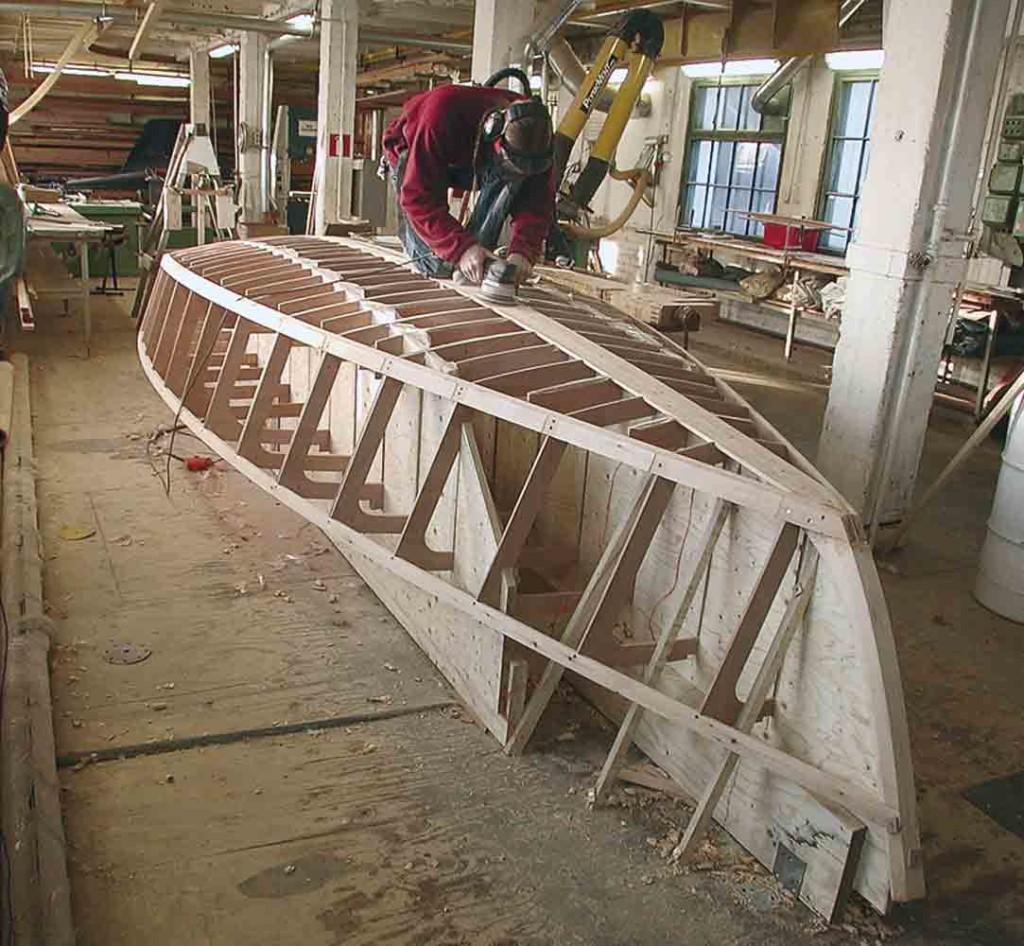 Kuva on perinteisen puukäsityön ja tietotekniikan kädenpuristus. Rakenteilla olevan Lightning-luokan veneen puuosista suurinosa on tietokoneleikattu puusta. Ympäristömme kannalta on tärkeää, että puuveneiden rakentamisen tekniikoita kehitetään kilpailukykyiseksi, muuten mustat pilvet varjostavat veneilyn tulevaisuutta.